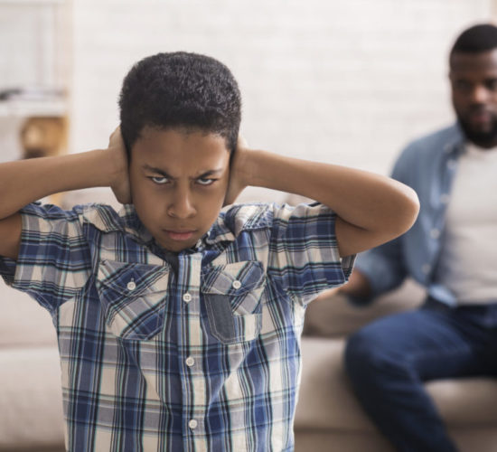 Disobedient Child. Preteen black boy closing ears not to listen father's scolding after his bad behavior, selective focus